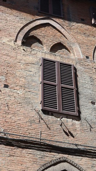 Siena 'Hole in wall' window overlaid on historic pointed arch facade